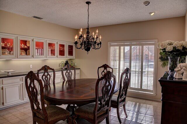 round dining table under a hanging chandelier